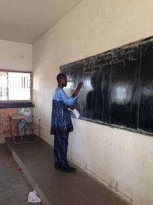 Mr. Ibrahima Seck writing instructions on the board.
